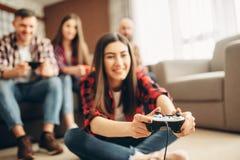 Los amigos con las palancas de mando juegan la consola de la TV en casa imágenes de archivo libres de regalías