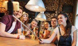 Los amigos con smartphone en selfie se pegan en la barra Imágenes de archivo libres de regalías