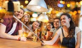 Los amigos con smartphone en selfie se pegan en la barra Foto de archivo libre de regalías