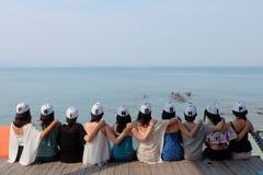 Los amigos de las mujeres con el casquillo de la AMISTAD sientan el cielo azul del mar del abrazo juntos Imagen de archivo
