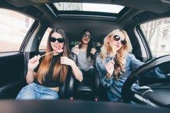 Los amigos de las mujeres jovenes con el caramelo se divierten cuando nuevo coche de la impulsión en viaje por carretera Imagen de archivo libre de regalías