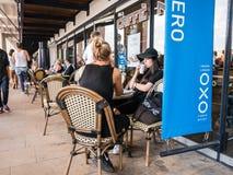 Los amigos de las mujeres se sientan en la tabla de Caffe Nero fuera del muelle oxo de la torre, S Fotos de archivo libres de regalías