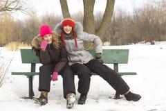 Los amigos de muchacha se sientan en banco Fotos de archivo libres de regalías