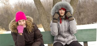 Los amigos de muchacha se sientan en banco Foto de archivo