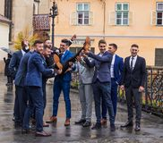 Los amigos del ` s del novio lo detienen delante de la iglesia en el pequeño cuadrado Ciudad de Sibiu en Rumania Imagen de archivo libre de regalías