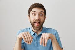 Los amigos dicen que su novia lo domesticó como perro Novio europeo divertido con la barba que hace la cara muda, pegando hacia f fotos de archivo libres de regalías