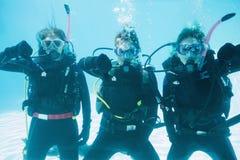 Los amigos en el entrenamiento del equipo de submarinismo se sumergieron en la piscina que mostraba los pulgares abajo Fotos de archivo