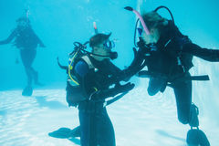 Los amigos en el entrenamiento del equipo de submarinismo se sumergieron en piscina Fotografía de archivo libre de regalías