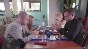 Los amigos en el restaurante pegado en sus teléfonos y se ignoran metrajes