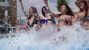 Los amigos en las chicas marchosas de un verano con las bebidas coloridas hacen las piernas de un chapoteo en el agua que se sien almacen de video
