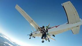 Los amigos en tándem del paracaidismo saltan del avión fotografía de archivo