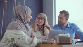 Los amigos están descansando en sitio y la charla, rubia está preguntando a mujer musulmán almacen de metraje de vídeo