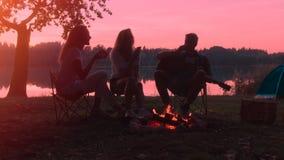 Los amigos están disfrutando de puesta del sol cerca de hoguera en el sitio para acampar en caminar almacen de video