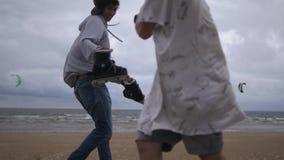 Los amigos extremos de los deportistas jocosamente luchan en la orilla de mar metrajes