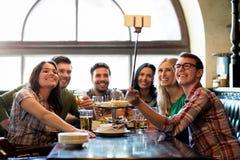 Los amigos felices con el selfie se pegan en la barra o el pub Foto de archivo libre de regalías