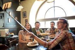 Los amigos felices con el selfie se pegan en la barra o el pub Fotos de archivo libres de regalías