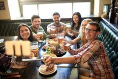 Los amigos felices con el selfie se pegan en la barra o el pub Imagenes de archivo