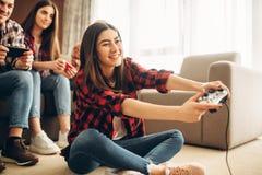 Los amigos felices con las palancas de mando juegan la consola video fotografía de archivo