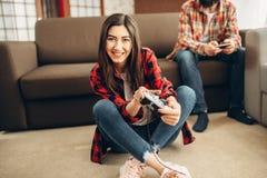 Los amigos felices con las palancas de mando juegan la consola video foto de archivo