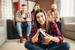 Los amigos felices con las palancas de mando juegan la consola video foto de archivo libre de regalías