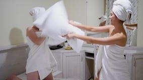 Los amigos felices de las muchachas alegres en toallas de baño se divierten y se baten con las almohadas en cama en dormitorio almacen de video