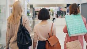 Los amigos felices de las mujeres jovenes están caminando juntos en el centro comercial que sostiene bolsos brillantes y que habl almacen de video