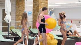 Los amigos felices en bañadores con el anillo y la bola inflables el verano de la terraza descansan almacen de video