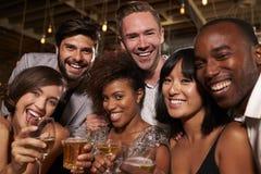 Los amigos felices en un partido en una barra miran a la cámara, cierre para arriba Foto de archivo