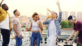 Los amigos felices están bailando en el partido del tejado mientras que DJ está trabajando con la consola de mezcla que lleva el  metrajes