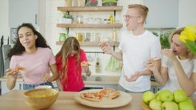 Los amigos felices están comiendo la pizza y se están riendo de la cocina almacen de metraje de vídeo