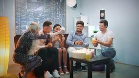Los amigos felices hacen una sorpresa para la muchacha del cumpleaños, han preparado una torta con las velas almacen de metraje de vídeo