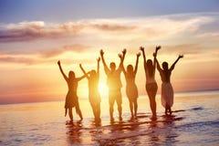 Los amigos felices miran puesta del sol sobre el agua foto de archivo