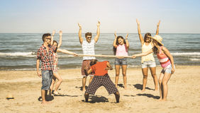 Los amigos felices multirraciales agrupan divertirse con el limbo en la playa fotos de archivo