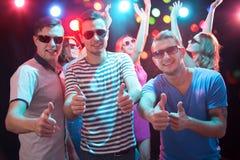 Los amigos felices que muestran la AUTORIZACIÓN firman en el club nocturno fotografía de archivo