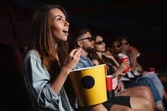 Los amigos felices que se sientan en cine miran la película el comer de las palomitas Fotografía de archivo