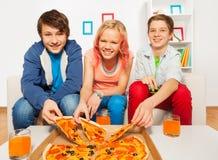 Los amigos felices que sostienen la pizza sabrosa juntan las piezas en casa Fotografía de archivo libre de regalías