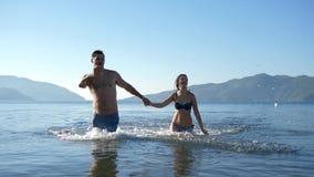 Los amigos felices salpican el agua y se divierten en el mar del verano almacen de video