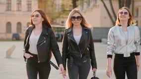 Los amigos femeninos combinan a las señoras confiadas que caminan la calle almacen de video