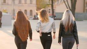 Los amigos femeninos combinan a las se?oras confiadas que caminan la calle almacen de video