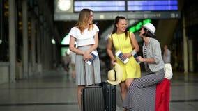 42ebe457f Los amigos femeninos divertidos están esperando juntos un avión en el  aeropuerto Retrato de tres mujeres