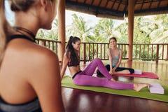 Los amigos femeninos durante clase de la yoga se rompen en el centro de aptitud Fotografía de archivo libre de regalías