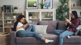 Los amigos femeninos en ropa informal están utilizando los smartphones que se sientan en el sofá en el apartamento Tecnologías mo metrajes