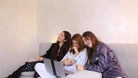 Los amigos femeninos miran películas de observación del tiempo de película en el ordenador portátil y sentarse en el sofá suave e almacen de video