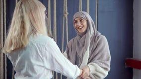 Los amigos femeninos musulmanes y occidentales se están encontrando en café, están abrazando y están disfrutando metrajes