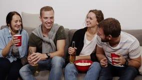 Los amigos femeninos y masculinos jovenes alegres con las bebidas se están sentando en el sofá en casa, comiendo las palomitas de almacen de video