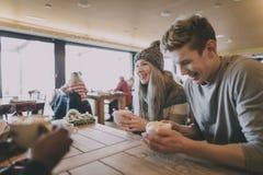 Los amigos gozan del café en invierno Imágenes de archivo libres de regalías