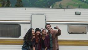 Los amigos hacen el selfie cerca de la caravana almacen de video