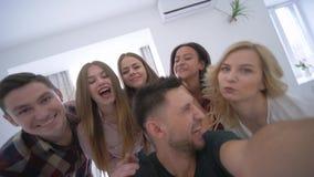 Los amigos hacen el selfie usando smartphone en el partido casero, mujeres jovenes y hombres engañando alrededor en cámara almacen de metraje de vídeo
