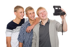 Los amigos hacen a uno mismo en la impresión inmediata de la cámara vieja Fotos de archivo libres de regalías