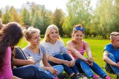 Los amigos internacionales felices se sientan juntos en prado Foto de archivo libre de regalías